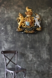 lifestyle image of Coat Of Arms Wall Plaque with black chair and distressed grey wall background