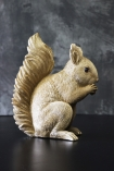 lifestyle image of Gold Squirrel Coin Bank from side on black table and distressed grey wall background
