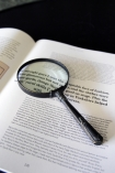 detail image of magnifying glass on open book