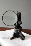 lifestyle image of Wonderland Rabbit Magnifying Glass on open book with grey wall background