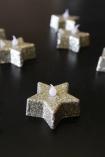 lifestyle image of Glitter Star Tea Lights - Gold turned off on black table