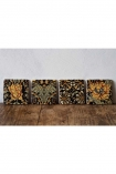 landscape lifestyle Image of the Set Of 4 Vintage Style Floral Ceramic Coasters standing up in a row on wooden surface with pale wall background