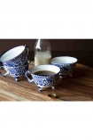 Lifestyle image of the Set Of 4 Pretty Indigo Blue & White Teacups on wooden shelf with milk bottle in background