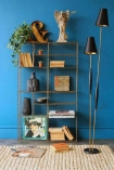 Room with a tall brass industrial storage rack in front of a bright blue wall floor lamp and books on the shelves lifestyle image