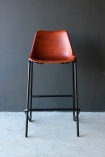 detail image of front of Industrial Leather Bar Stool - Brown on grey flooring and dark grey wall background