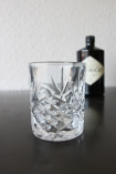 lifestyle image of Old Fashioned Crystal Style Tumbler - Clear on black background with hendricks bottle and pale wall background