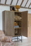 Lifestyle image of the Timber Strips Shelved Storage Cabinet with the right door open