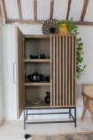 Lifestyle image of the Timber Strips Shelved Storage Cabinet with the left door open