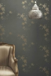 lifestyle image of Barneby Gates All Star Wallpaper - Gun Metal - SAMPLE with gold armchair and silver ceiling light