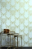 lifestyle image of Barneby Gates Deer Damask Wallpaper - Duck Egg Blue/Antique Gold - SAMPLE with nest of three tables with books on top