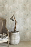 lifestyle image of Barneby Gates Fresco Birds Wallpaper - SAMPLE with wooden armchair and gold table lamp on white side table