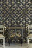 lifestyle image of Barneby Gates Honey Bees Wallpaper - Gold on Charcoal - SAMPLE with black and gold cabinet and two chairs