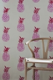 lifestyle image of Barneby Gates Pineapple Wallpaper - Pink/Red - SAMPLE with wooden chair in front