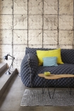 lifestyle image of NLXL TIN-03 Brooklyn Tin Tiles Wallpaper By Merci - SAMPLE with grey sofa with yellow and blue cushions and wooden coffee table