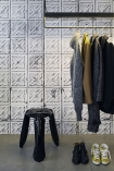 lifestyle image of NLXL TIN-04 Brooklyn Tin Tiles Wallpaper By Merci - SAMPLE with black clothing rack with clothes on and black stool