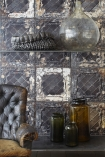 lifestyle image of NLXL TIN-07 Brooklyn Tin Tiles Wallpaper By Merci - SAMPLE with leather armchair and apothecary jars with large glass vase and concrete ornament on shelf