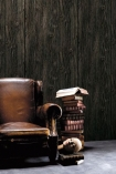 lifestyle image of Koziel Charred Wood Boarding Wallpaper - SAMPLE with brown leather armchair and pile of books