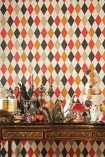 lifestyle image of Cole & Son Whimsical Collection - Punchinello Wallpaper - Multicoloured 103/2006 - ROLL with wooden table and many ornaments on top