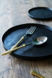 lifestyle image of Faria Black Serving Platter with fork and spoon and other crockery on wooden table