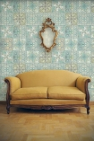 lifestyle image of Louise Body Patchwork Jade Tile Wallpaper - SAMPLE with yellow sofa and wall mirror
