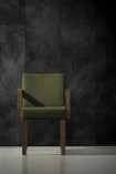 lifestyle image of NLXL CON-07 Concrete Wallpaper by Piet Boon - SAMPLE with green armchair and grey flooring