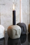 Close-up image of the Toby Quirky Face Candle Holder In Natural with a candle in him