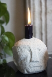Close-up image of the Ollie Quirky Face Candle Holder In White with a candle in him