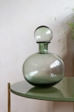 Lifestyle image of the Round Green Glass Decanter with Ball Stopper