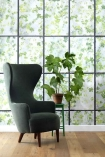 lifestyle image of NLXL Labs Wallpaper - ERG 01 Greenhouse by Erik Gutter - SAMPLE with green tall armchair and house plant on black side table