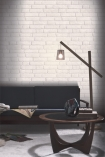 lifestyle image of Koziel White Brick Wallpaper - SAMPLE with dark grey sofa and floor lamp and round wooden coffee table