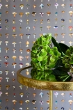 lifestyle image of 17 Patterns Forager Wallpaper - 4 Colours Available with gold side table and green plant on top