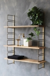 lifestyle image of Adjustable Brass & Wood Wall Shelf with bathroom accessories and plant hung on distressed grey wall background