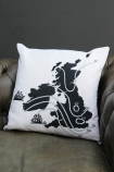 lifestyle image of Ali Miller UK & Ireland Map - Home Sweet Home Cushion on grey leather sofa and dark grey wall background