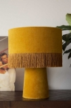 lifestyle image of All Over Velvet Table Lamp With Fringe - Mustard on black table with plant and picture frame with pale wall background