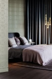 Lifestyle shot of the green tile wallpaper in a bedroom with a made bed and golden pendant lights - Rockett St George