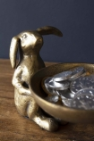 lifestyle image of Antique Brass Effect Bunny Trinket Bowl with silver chocolate coins inside on wooden table and dark wall background