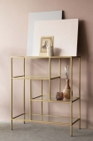 lifestyle image of Antique Brass & Glass 4-Tier Shelf Unit with canvases and other decor on top on grey flooring and pale wall background