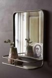 Lifestyle image of the Antique Silver Almost Square Bathroom Mirror With Shelf with plant in pot on shelf with dark wall background