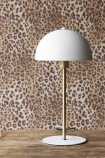 Lifestyle image of the Art Deco Canopy Table Lamp - Matt White on wooden surface and with Rockett St George Leopard Love Wallpaper in the background