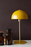 Lifestyle image of the Art Deco Canopy Table Lamp - Ochre Gold on marble table with apothecary style pots and dark wall background