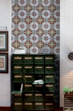 lifestyle image of Art Deco Wallpaper with black drawer unit and picture frames hung on wall