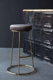 Lifestyle image of the Atlantis Velvet Bar Stool in Mushroom with tin tile bar in background on grey flooring and dark wall background