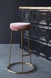 Lifestyle image of the Atlantis Velvet Bar Stool in Rose Pink with tin tile bar in background on grey flooring and dark wall background