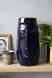 lifestyle image of Azul Blue Deep In Thought Face Vase on crowded wooden shelf with plant, picture frame and tea light holder with pale grey wall background