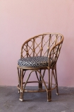 lifestyle image of Bamboo Chair on grey floor and pink toned wall background
