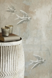 detail lifestyle image of Barneby Gates Fresco Birds Wallpaper with side table with book and candles on in front