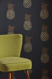 lifestyle image of Barneby Gates Pineapple Wallpaper - Charcoal with green armchair in front