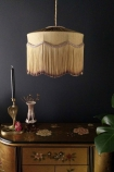 Lifestyle image of the Bespoke Inca Gold Silk Tiffany Lamp Shade over chest of drawers with ornaments on top with dark wall background