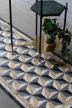 lifestyle image of Beija Vinyl Floor Runner - Antique Geometric on floor with two black side tables and plant in gold pot