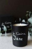 lifestyle image of Bella Freud Je T'aime Jane Candle on marble counter with eucalyptus on and dark wall background